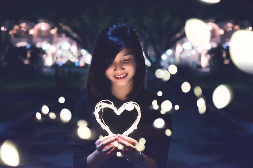 Femme tenant un coeur lumineux