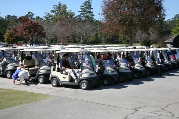 Teams assemble in their golf carts at the start of the tournament.