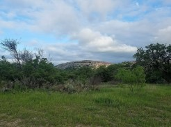 Enchanted Rock with puffy clouds above.