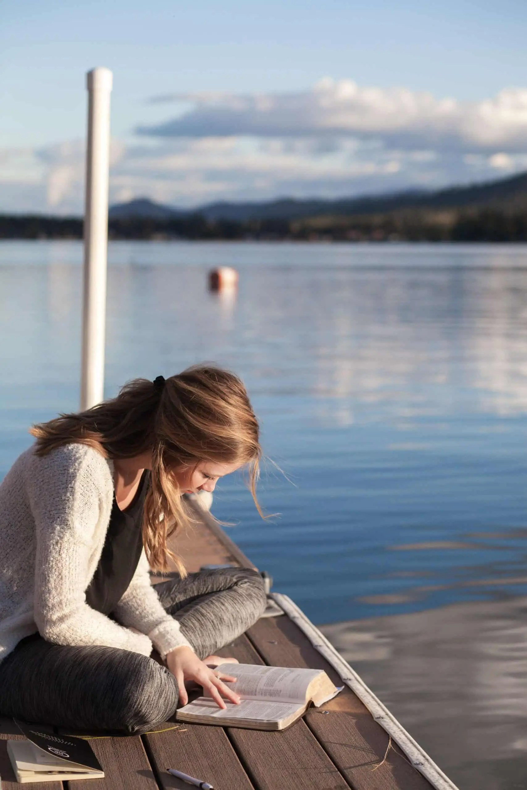 woman bible by water