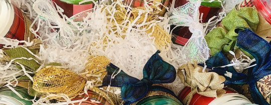 A tin basket with white filler and glass candles decorated with wrapping paper and ribbon.