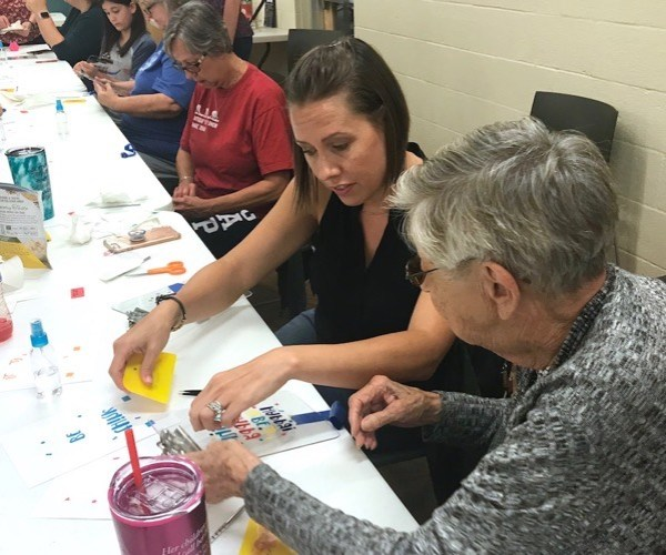 Young woman helping her grandmother during craft class