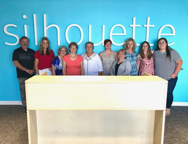 Group of people in front of Silhouette sign