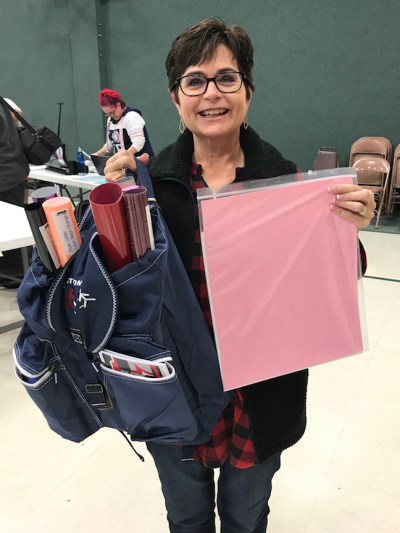 Woman with prize of Siser adhesive and heat transfer vinyl.