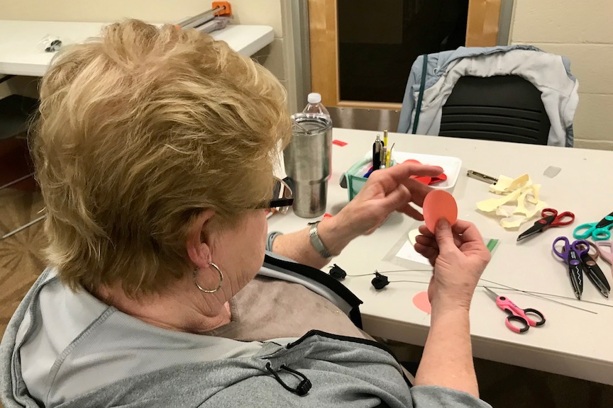 Woman working on crepe paper flowers at craft class