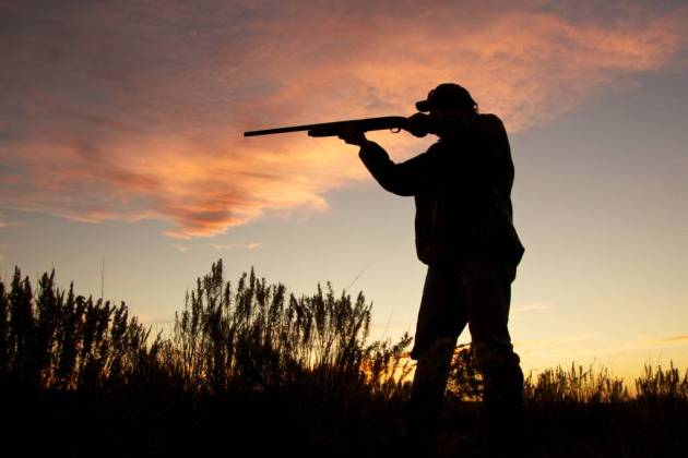 Hunter Silhouetted Shooting at Sunset
