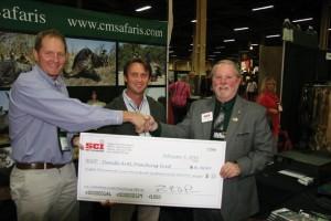 Presidente SCI Larry Higgins (derecha) entrega el cheque a Myles McCallum (izquierda) y Buzz Charlton (centro).