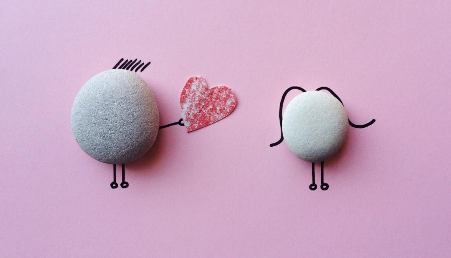 Two pebbles on a pink background with drawings