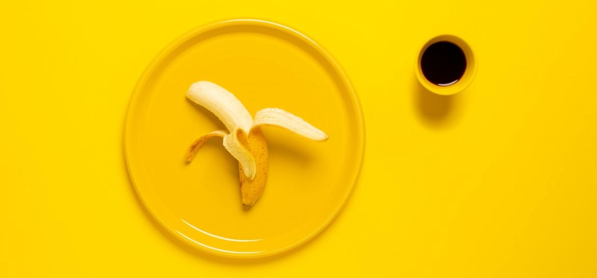 Banana and coffee on yellow background