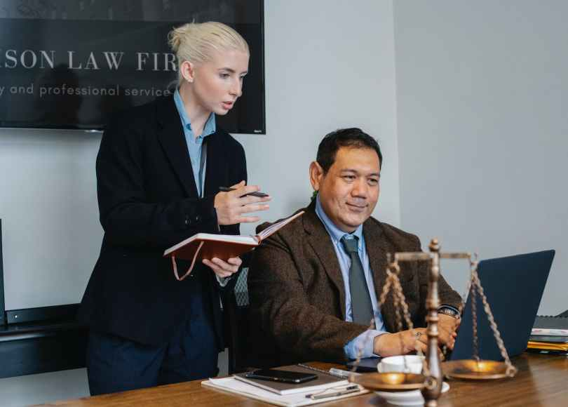 ethnic male lawyer showing document on laptop to young female colleague