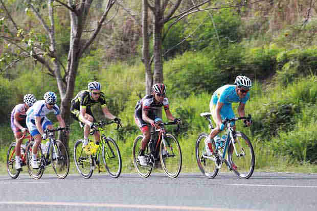 Cyclists negotiate an uphill road during the cycling tour 2015 edition.
