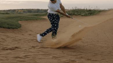 un golfeur qui engage sa frappe de balle sur le terrain