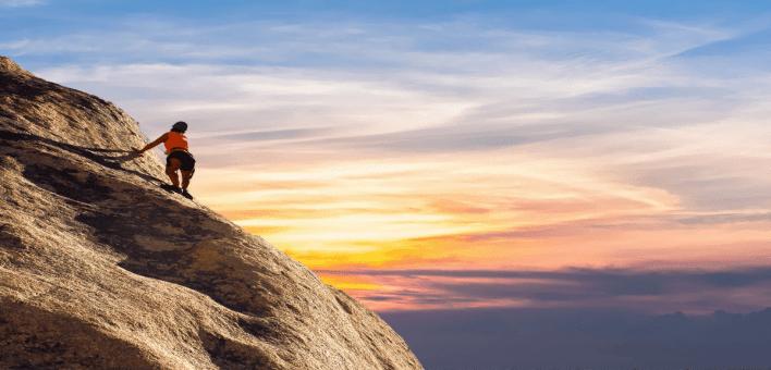 un alpiniste qui se trouve en haut d'une montagne en train d'admirer le coucher du soleil