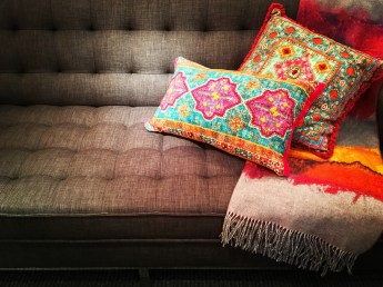 Textile sofa decorated with bright ornate cushions. Stylish furniture.