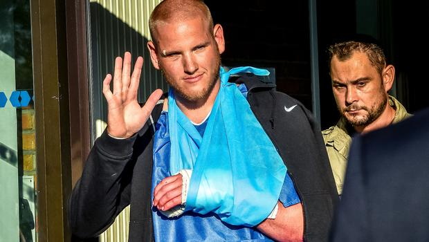 Off-duty U.S. Air Force Airman Spencer Stone, left, one of the men to overpower the gunman who opened fire with an assault rifle on a high-speed train, gestures as he leaves the hospital in Lesquin, northern France, Aug. 22, 2015.