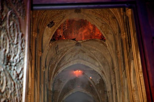 On voit des flammes alors que l'intérieur continue de brûler à l'intérieur de la cathédrale Notre-Dame de Paris.