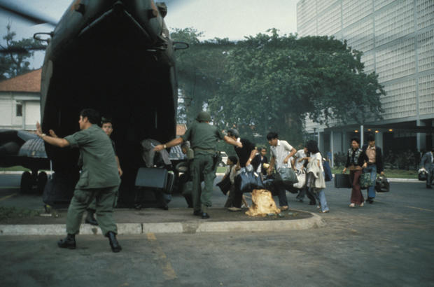 Americans and family members board a helicopter at the U.S. embassy during the Saigon fall in April 1975