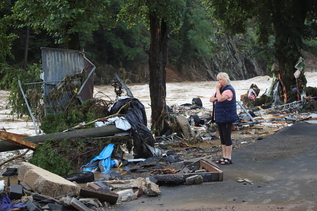 A woman looks at the rubble that caused the flooding beside the Ahr. brought with it
