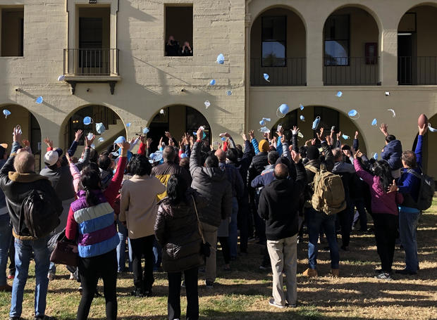 People evacuated from the epicenter of the coronavirus outbreak in China celebrate the end of their quarantine at March Air Reserve Base in Moreno Valley, California, on February 11, 2020.