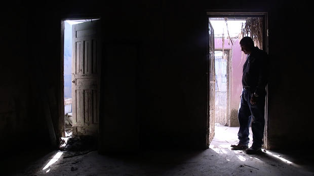 Man silhouetted in damaged house in Honduras