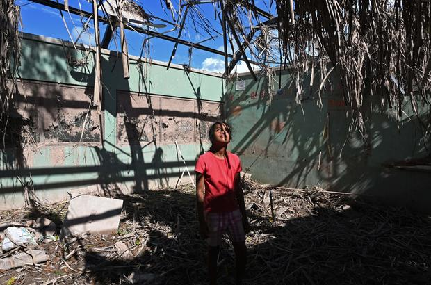 Girl stands in roofless house destroyed by hurricanes in Honduras