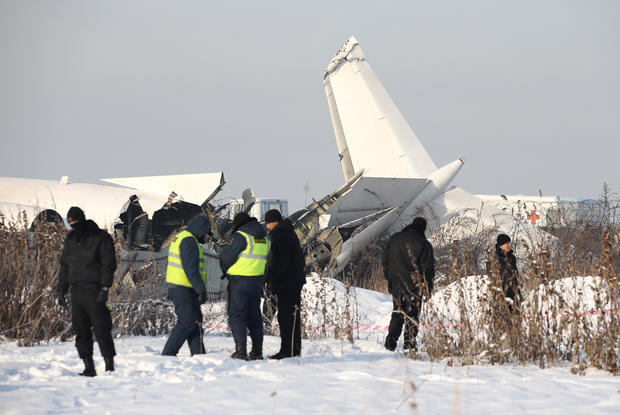 Emergency and security personnel are seen at the site of a plane crash near Almaty