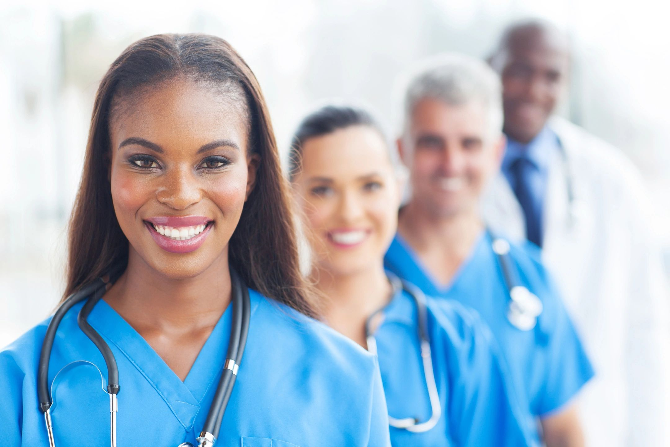 Four healthcare workers stand in a line going away from the camera