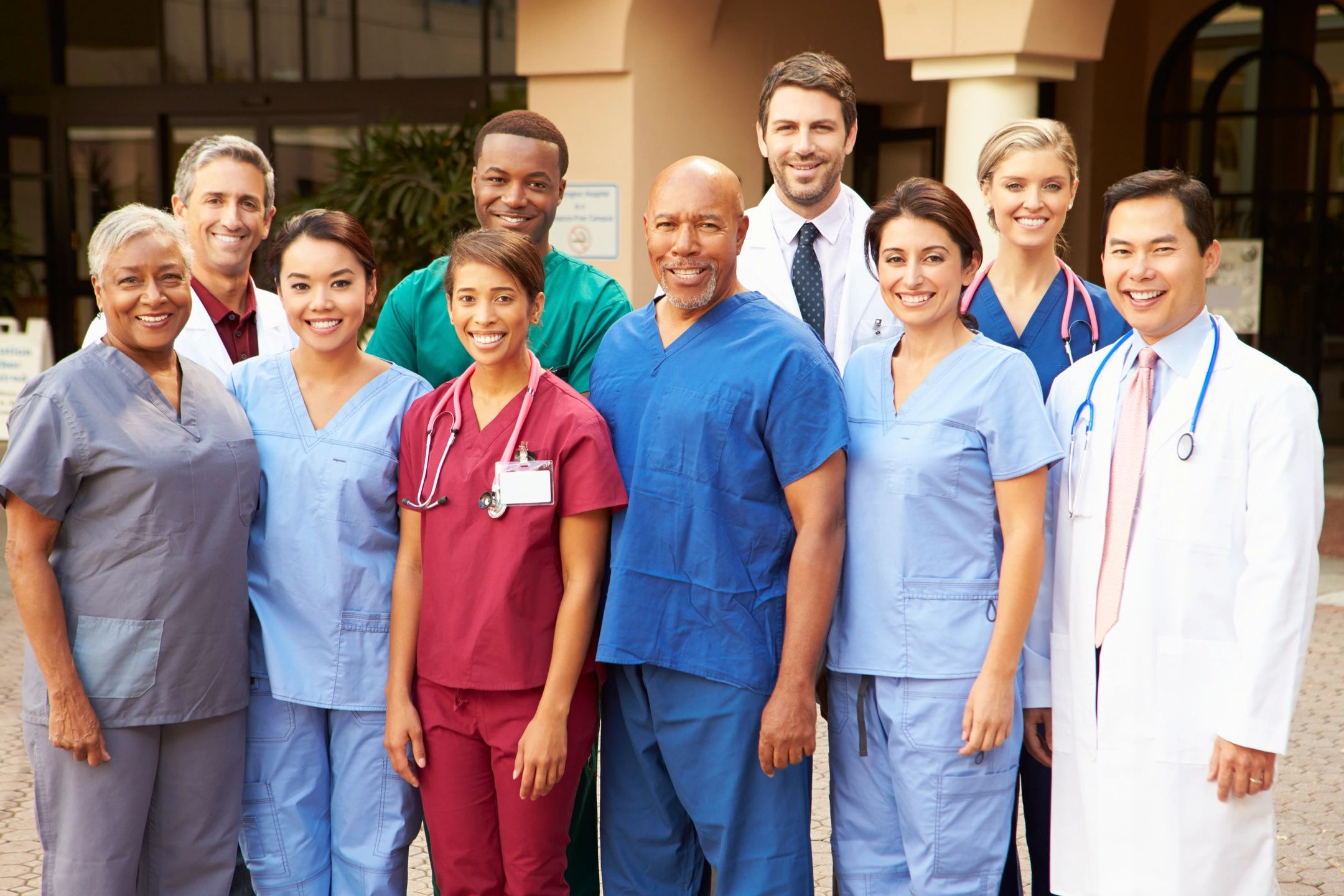 Diverse group of ten medical professionals of many ages, races, and genders standing outside of a building. 7 are in scrubs of various colors and three are wearing white coats.