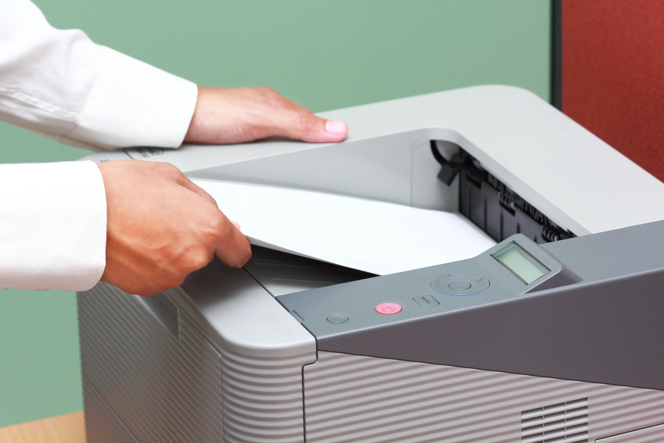 Hands taking a paper from a printer