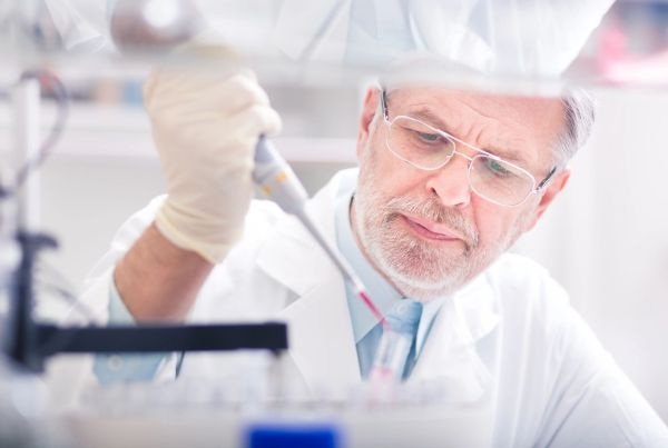 Older man in lab coat with gloves inserting liquid into a vial