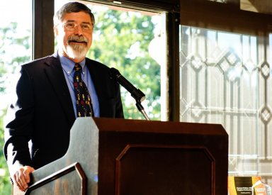 Michael Taylor, MD, former College professor and chair of the Department of Pediatrics, addresses graduating residents at June ceremony.