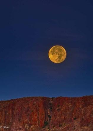 Full moon setting as sun is rising