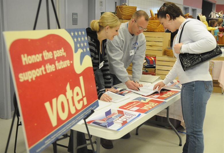 A voting sign and someone checking in at a table. Military voting. Photo by U.S. Military. Creative Commons License