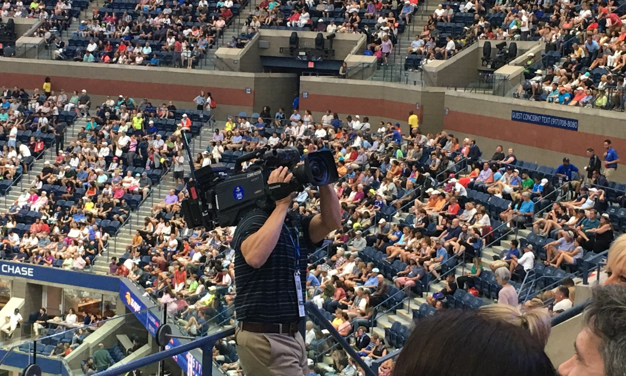 Videographer at the U.S. open with a live camera shooting the audience.