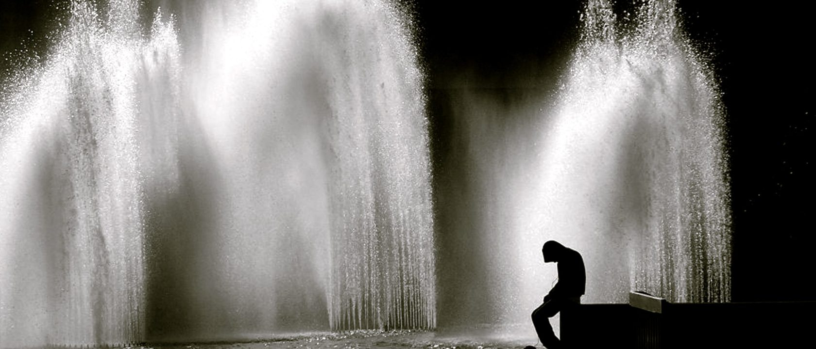 silhouette of young man sitting next to a fountain, black and white photo
