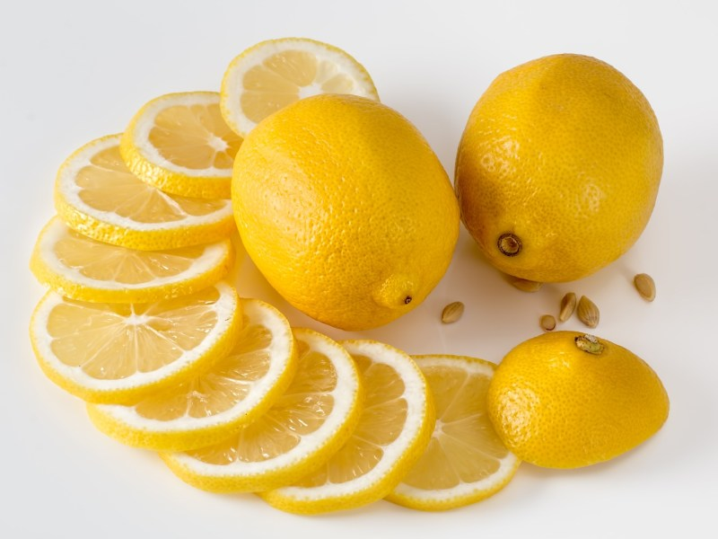 Whole and sliced lemons on a white background