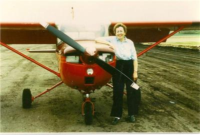 Mary Payne in the 50s or 60s standing by a red propeller plane