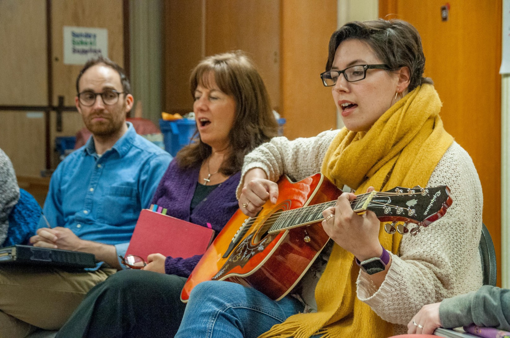 Bri-anne leads the circle in song. With David and Karen.