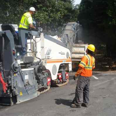 Crews grind asphalt along Blagen Road.