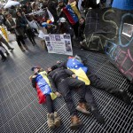 People imitate dead bodies as they lie on the ground in protest at what they say is an oppressive regime in Venezuela, in Times Square in New York