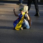 An opposition demonstrator sits blocking the city's main highway during a protest against Nicolas Maduro's government in Caraca