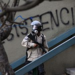 A national policeman walks past a graffiti reading 'Resistance' during anti-goverment protests at Altamira square in Caracas