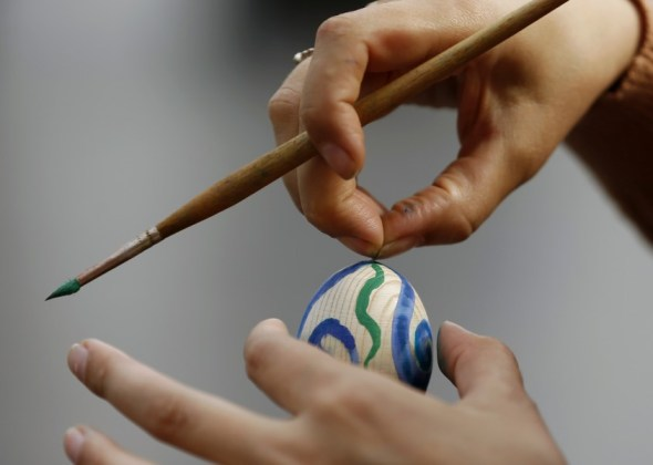 Ukrainian woman paints an artificial egg on the eve of Easter ahead of midnight Easter mass in Luhansk