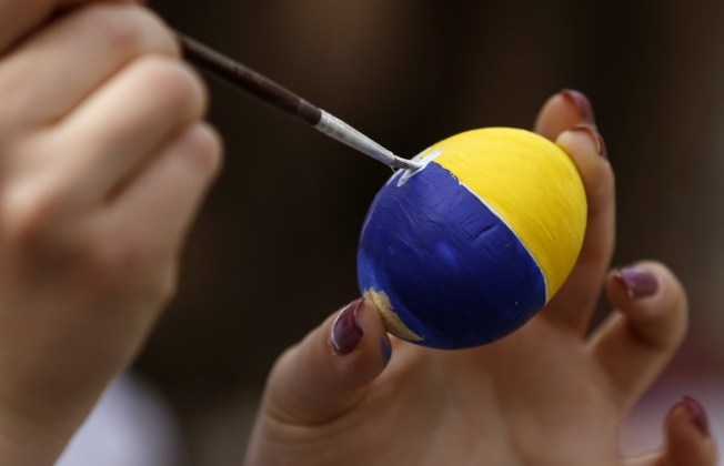 A woman paints an artificial egg on the eve of Easter ahead of midnight Easter mass in Luhansk