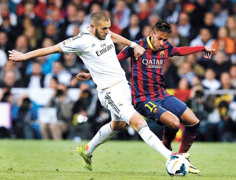Enfrentamiento. Benzemá (blanco) domina el balón ante la marca de Neymar en un cotejo de Liga.