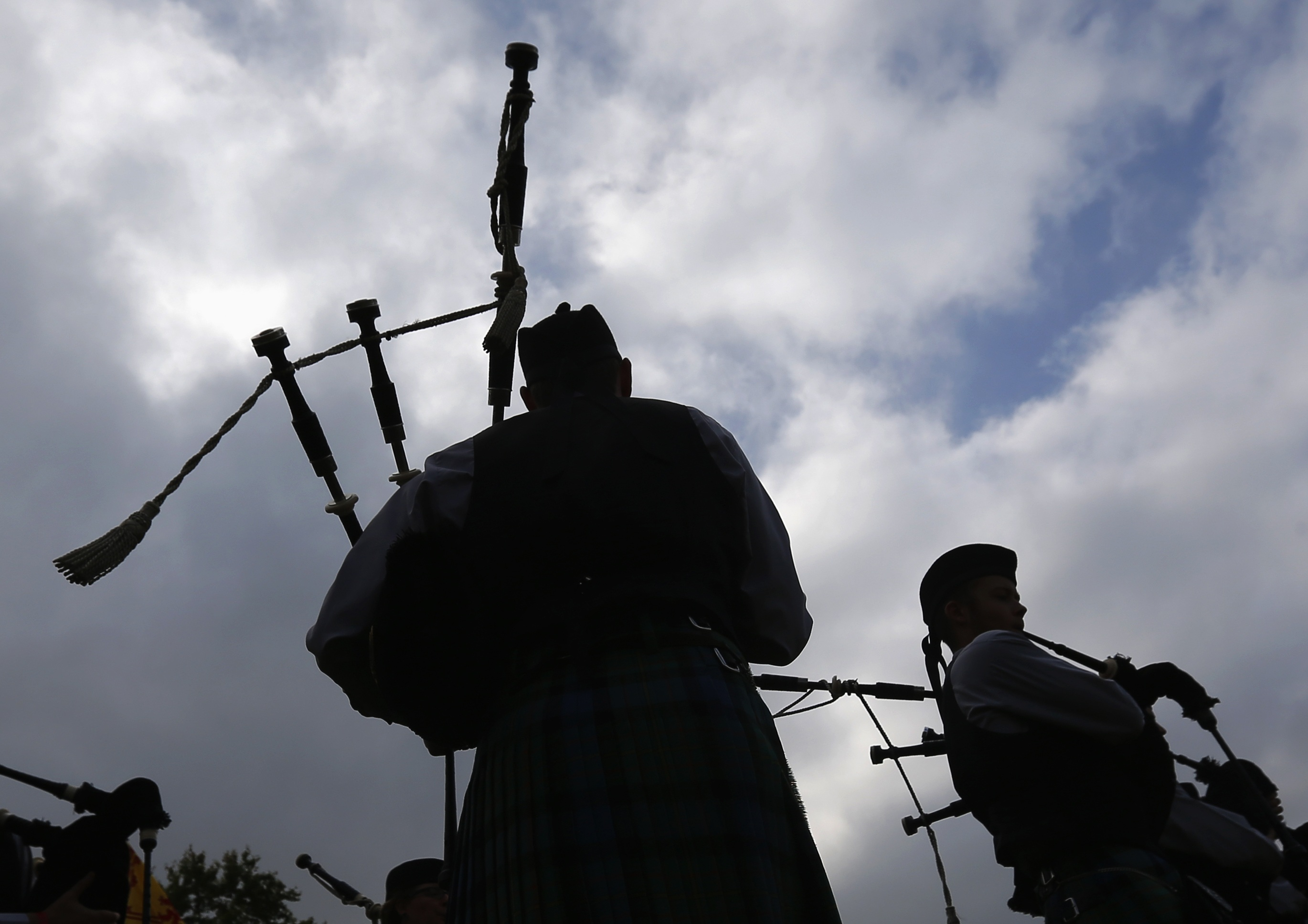 Competitors are silhouetted as they take part in the Belgian Pipe Band Championship during the Scottish Weekend event in Belgium's Flanders village of Bilzen