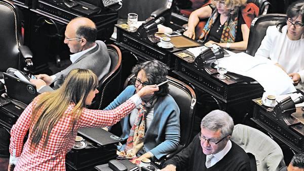 Bajada de línea. Juliana Di Tullio, jefa del bloque de diputados kirchneristas, le hace gestos ayer a su tropa en el recinto para ordenar el debate sobre la polémica ley de abastecimiento./DIEGO DIAZ