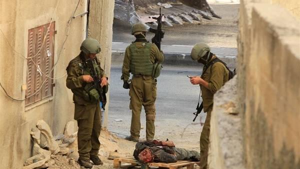 Soldados israelíes, junto al cuerpo de uno de los sospechosos de la muerte de tres chicos judíos en Hebrón, Cisjordania. (AFP)
