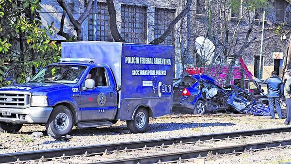 Tragedia. El auto arrollado detrás de la camioneta de la morgue. El tren lo arrastró varios metros. Los vecinos dicen que el paso a nivel es peligroso y las señales son confusas. /ALFREDO MARTINEZ