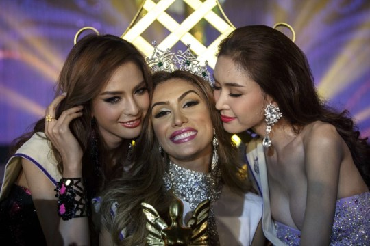 Isabella Santiago of Venezuela is kissed by runner-ups after she was crowned Miss International Queen in Pattaya